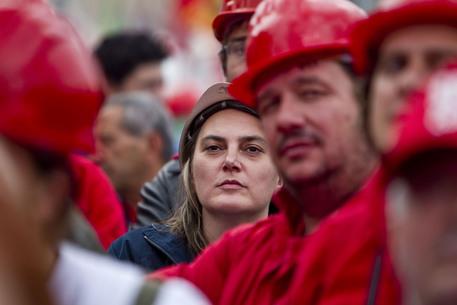 Partecipanti alla manifestazione della Fiom, questo pomeriggio 16 ottobre 2010 in piazza San Giovanni a Roma. E' il rosso a dominare piazza San Giovanni in Laterano a Roma dove stanno manifestando gli operai della Fiom. Tante le bandiere della sigla sindacale dei metalmeccanici, Cgil e Rifondazione comunista. Le uniche diverse sono quelle di colore bianco dell'Italia dei valori. La rete studentesca sta mostrando uno striscione con su scritto ''Gelmini dimettiti ricostruiamoci il futuro'' mentre alcune tute blu espongono cartelli con slogan: ''l'indifferenza uccide'', ''gli operai producono per tutti, rispettateli'', ''uniti contro il capitale''. Non mancano critiche al segretario della Cgil; su un cartello si legge ''Epifani con Cisl e Uil lascia stare. C'e' bisogno di lottare''.  ANSA/MASSIMO PERCOSSI